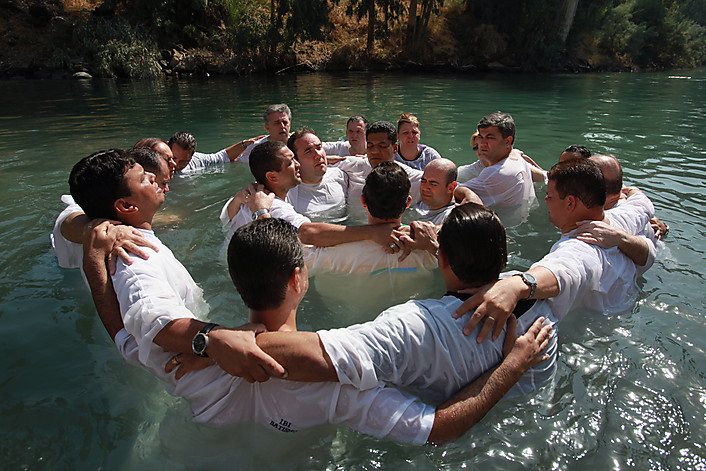 YARDENIT, ISRAEL - OCTOBER 04:  Brazilian Evangelist Christians embrace in prayer during their mass baptism ceremony in the Jordan River on October 4, 2009 at Yardenit in northern Israel. Hundreds of worshippers from northern Brazil immersed themselves in the biblical river as part of their pilgrimage to the Holy Land.  (Photo by David Silverman/Getty Images)